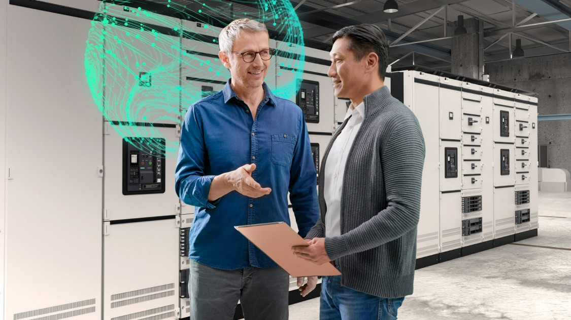 Two men talking in front of a control panel; a 3WA air circuit breaker in the background with a stylized digital impression symbolizes digitalization