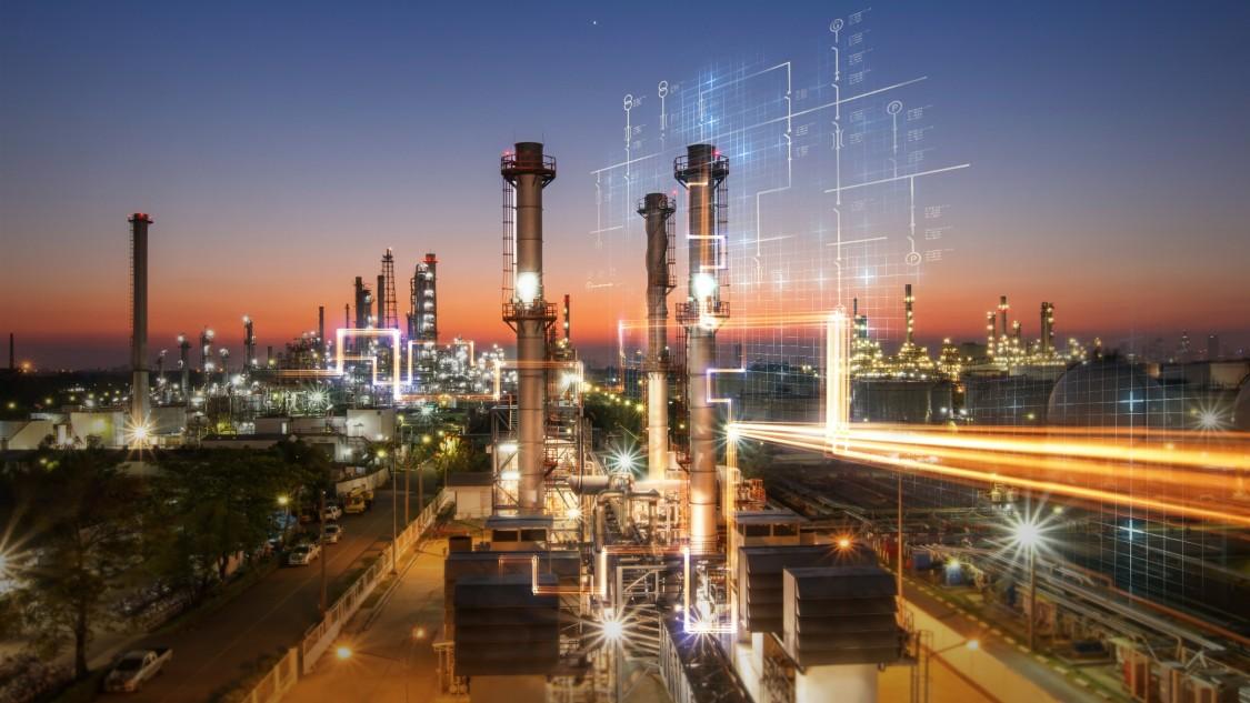 Nächtlicher Blick über eine weitläufige Industrieanlage mit digitalen Elementen, die eine integrierte Stromversorgung symbolisieren.
