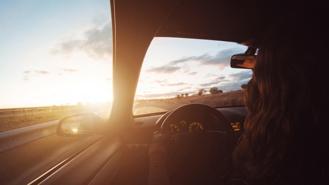 Eine Frau fährt mit offenem Fenster auf einer Landstraße, vor ihr der Sonnenuntergang
