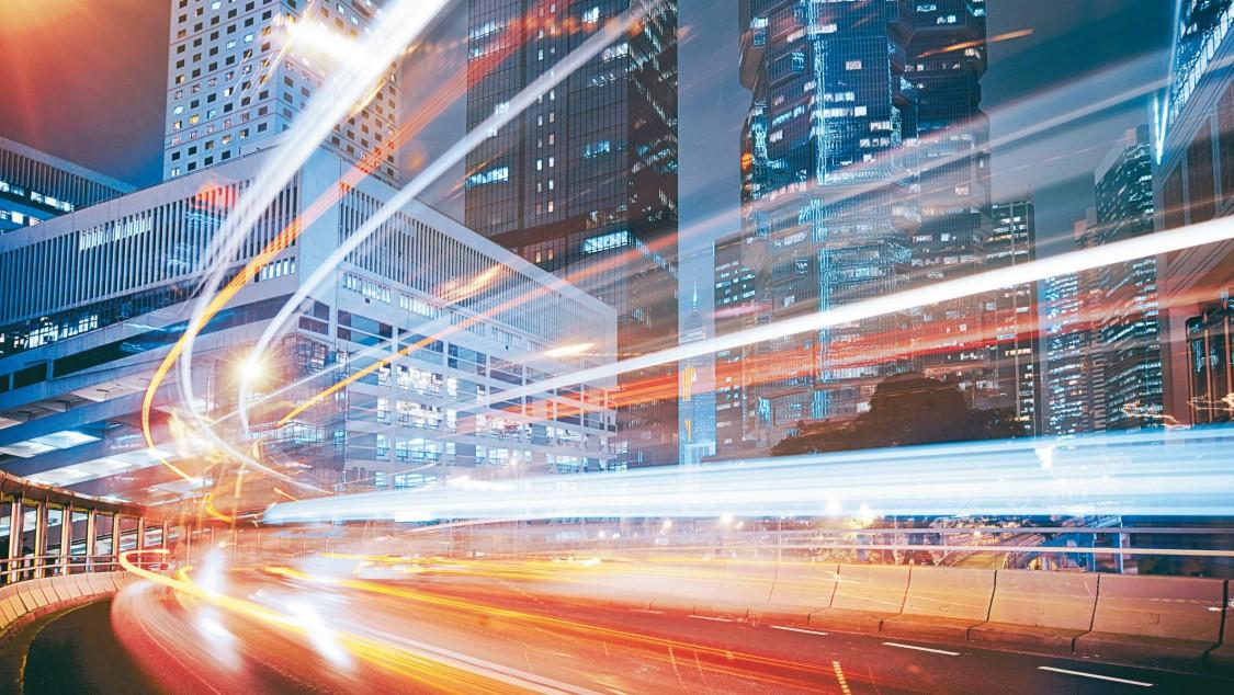 imagem noturna de uma cidade com luzes de trafego representando as tecnologias de uma cidade do futuro