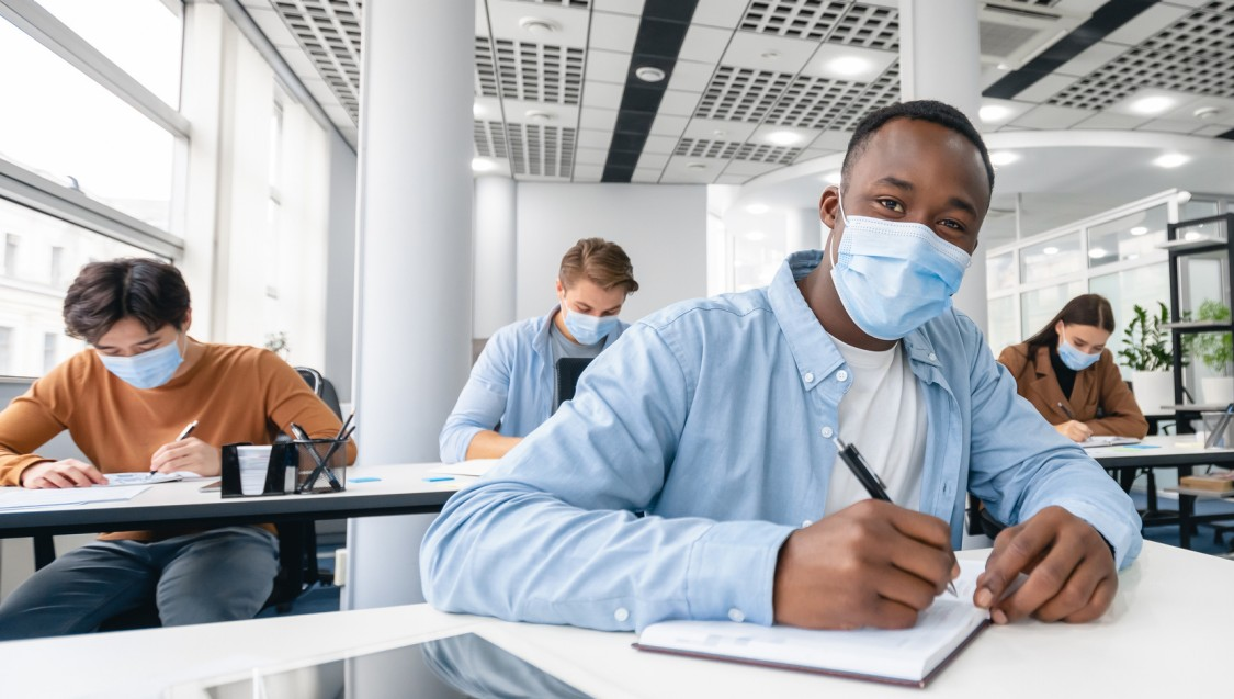 young man in classroom with other students during covid pandemic