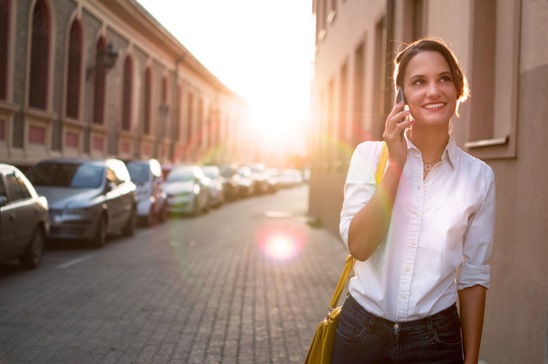 A young woman stands next to a street with a typical city appearance and makes a call on her Smartphone