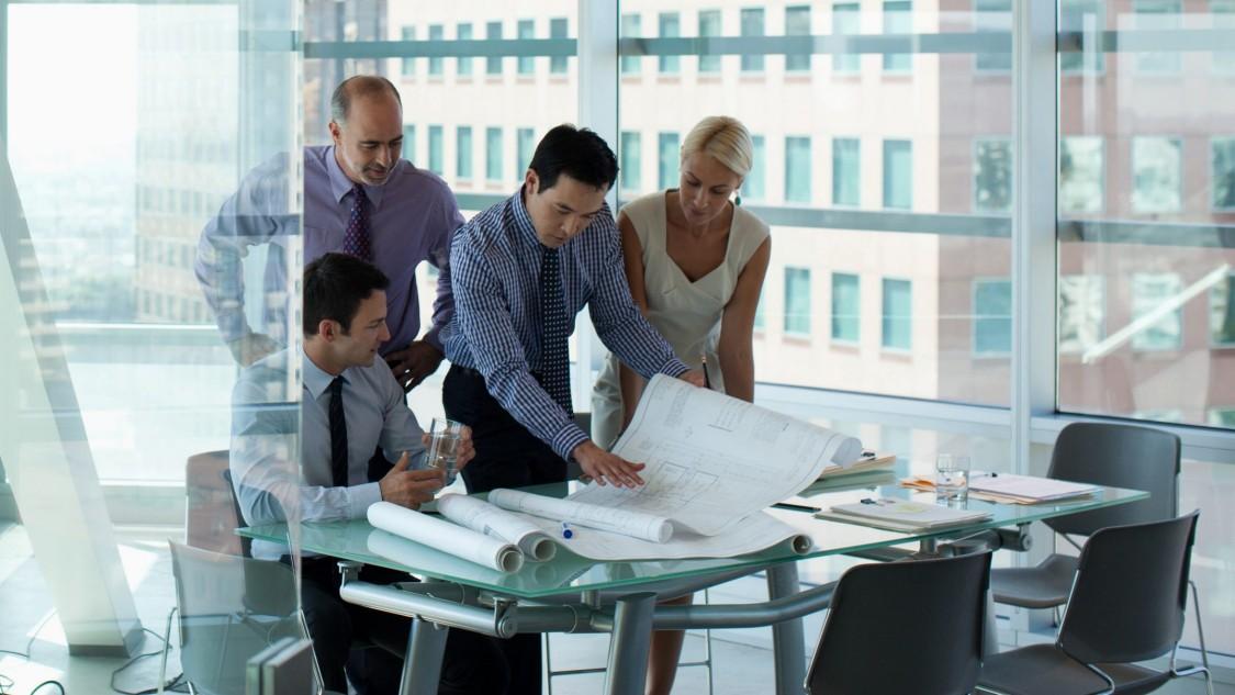Beratungsszene in einem Büro. Frontalaufnahme von einem  Mann sitzend sowie 2 Männern und einer Frau stehend, die gemeinsam auf große Pläne aus Papier blicken.