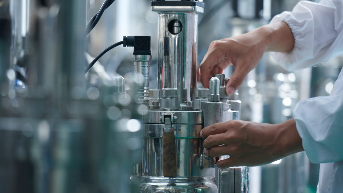 An employee at Cathay's bio-manufacturing plant takes a sample while a process is running.