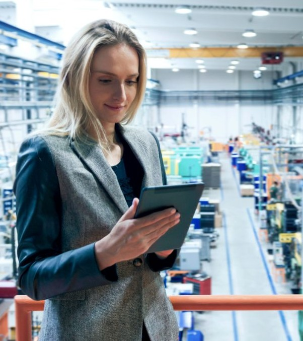 Horizontal color image of blond business female worker standing on balcony on top of large factory, holding digital tablet and examining the production online.