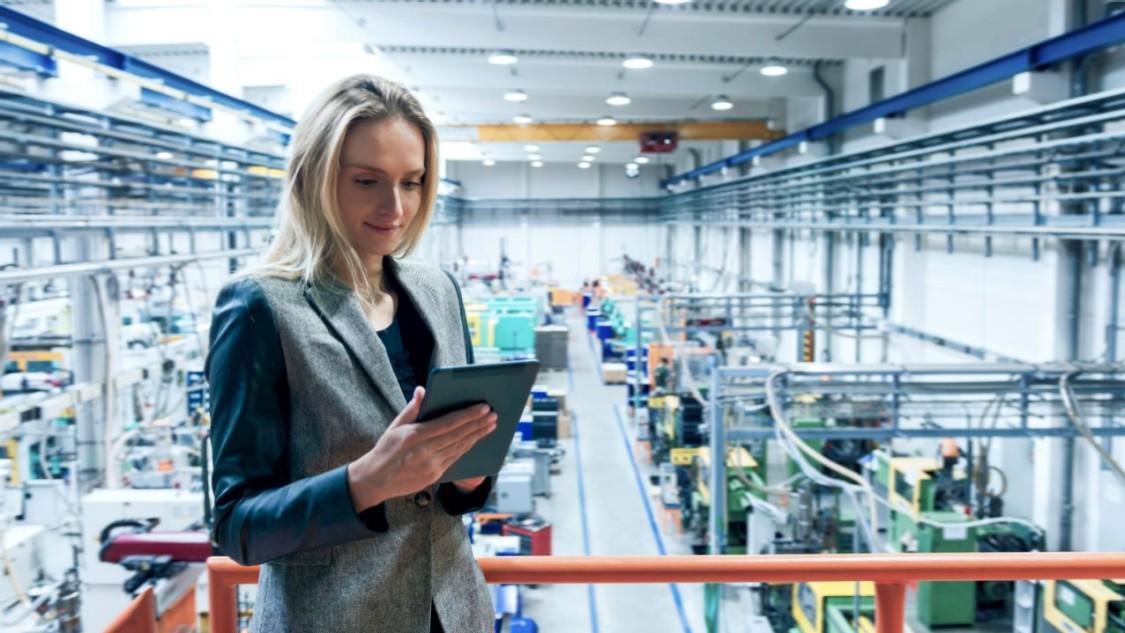 Woman on iPad standing on balcony of factory