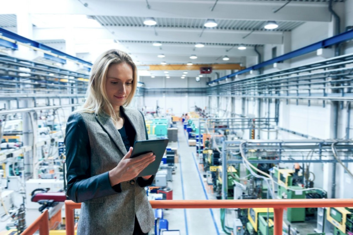 Woman holding iPad in manufacturing factory