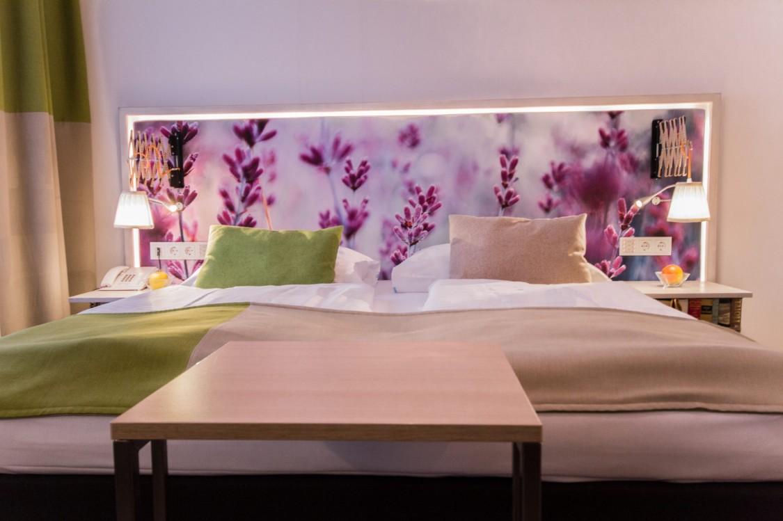 cama de casal com painel de fundo decorado com flores roxas, duas lâmpadas de cabeceira e roupa de cama beje e verde