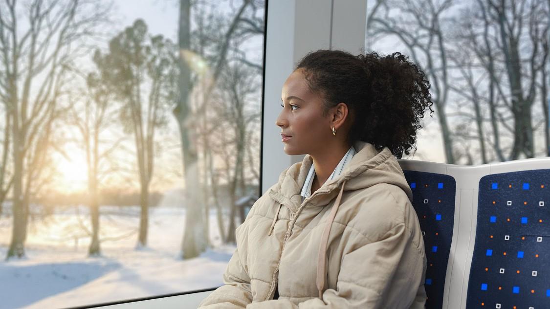 Eine junge Frau fährt in einer Siemens Mobility Inspiro Metro durch eine winterlicher Landschaft in Oslo.