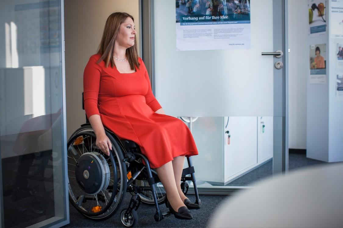 Marina bewegt sich mit ihrem Rollstuhl in den Büroräumen