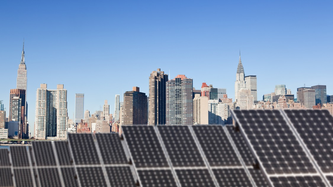 Roof top solar installation with Midtown Manhattan view as background, Chryler Building and Empire State Building.