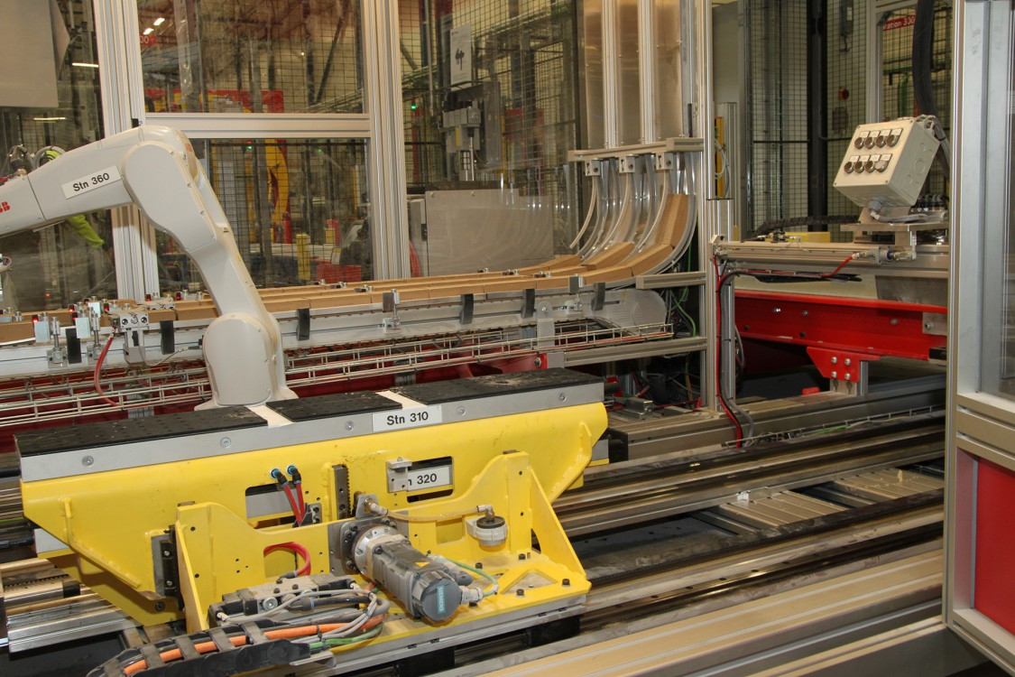 En robot plockar klossar, i olika storlekar och mängd, till båda wellklossappliceringslinjerna och bygger upp mönster efter vikt, ömtålighet etc. Klossarna sugs fast med vakuum. Skytteln, driven av servon i olika axlar, transporterar klossarna förbi limmunstycken som lägger på limsträngar enligt recept och pressar fast klossarna på godset och som styrs via TM-utgångar på PN-IRT och Simatic ET 200SP-nod. Hastigheten är hela 90 m/min, det vill säga 1 500 mm/sek.