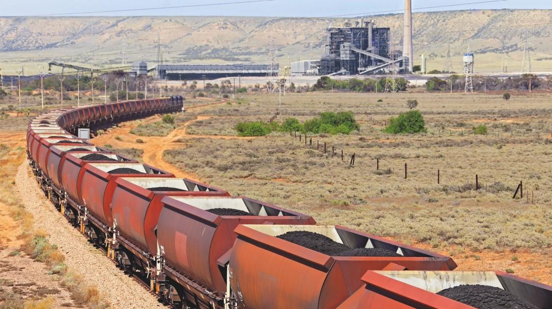 kilometerlanger Güterzug mit Fracht fährt durch eine Wüste