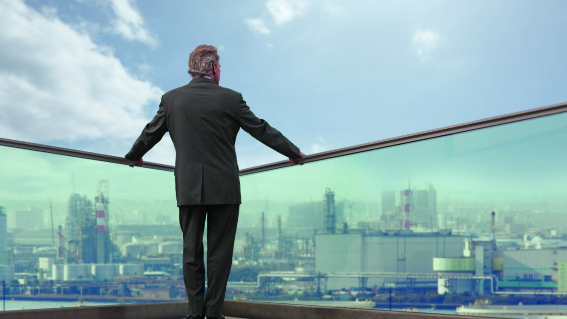 We see the back of a man standing at a transparent parapet, high above a city that he's looking down on.