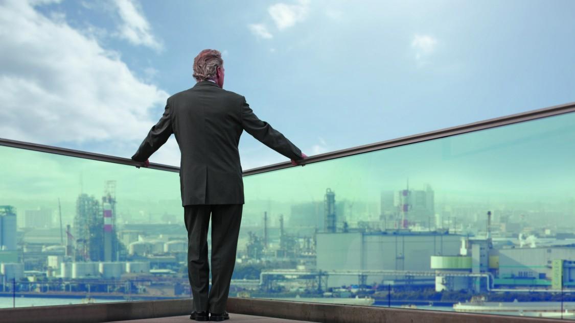 executivo de cabelos brancos está em uma varanda no topo de um prédio adimirando um setor industrial de uma metrópole