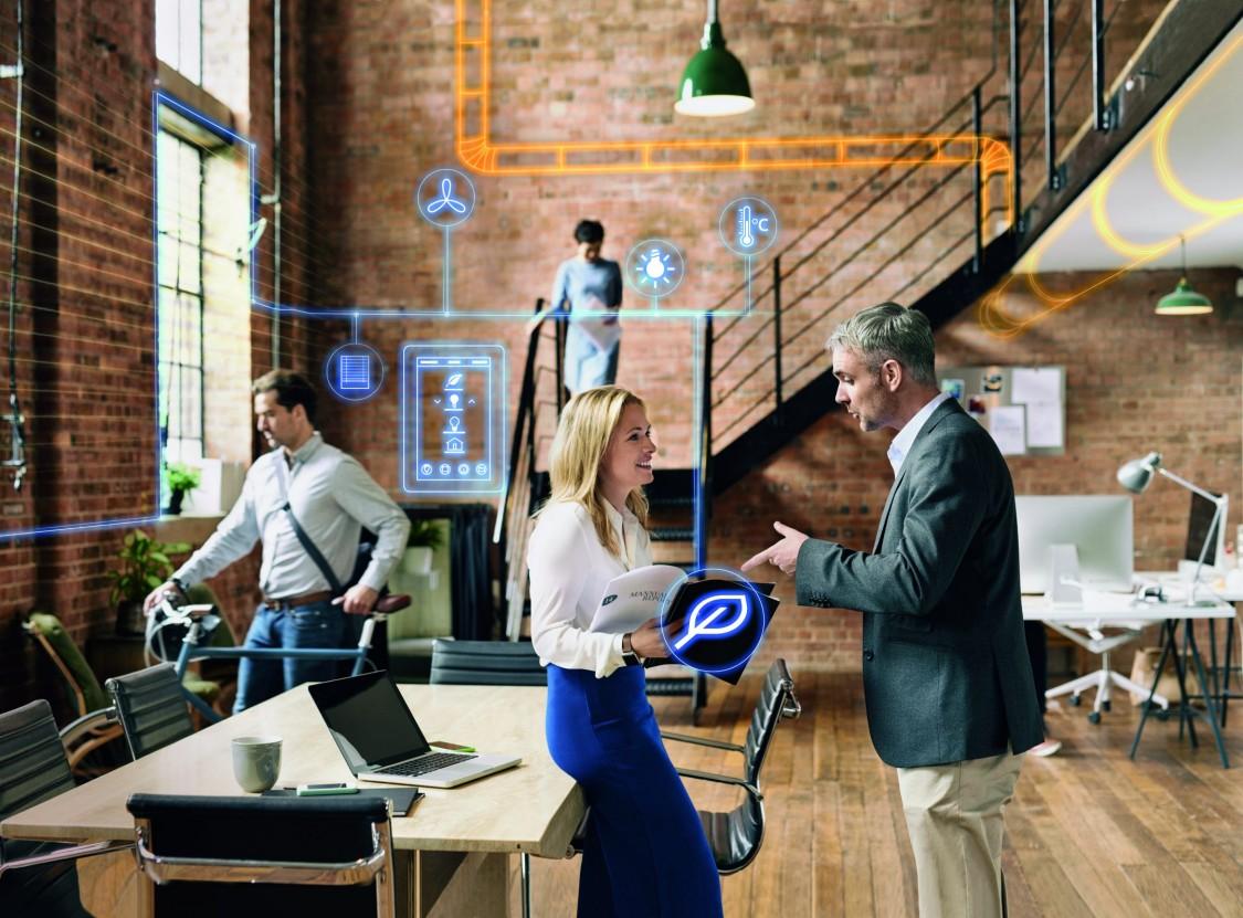 Mand og kvinde i samtale på kontor omgivet af ikoner, der markerer, hvordan indeklimaet kan styres med CTS-systemer.