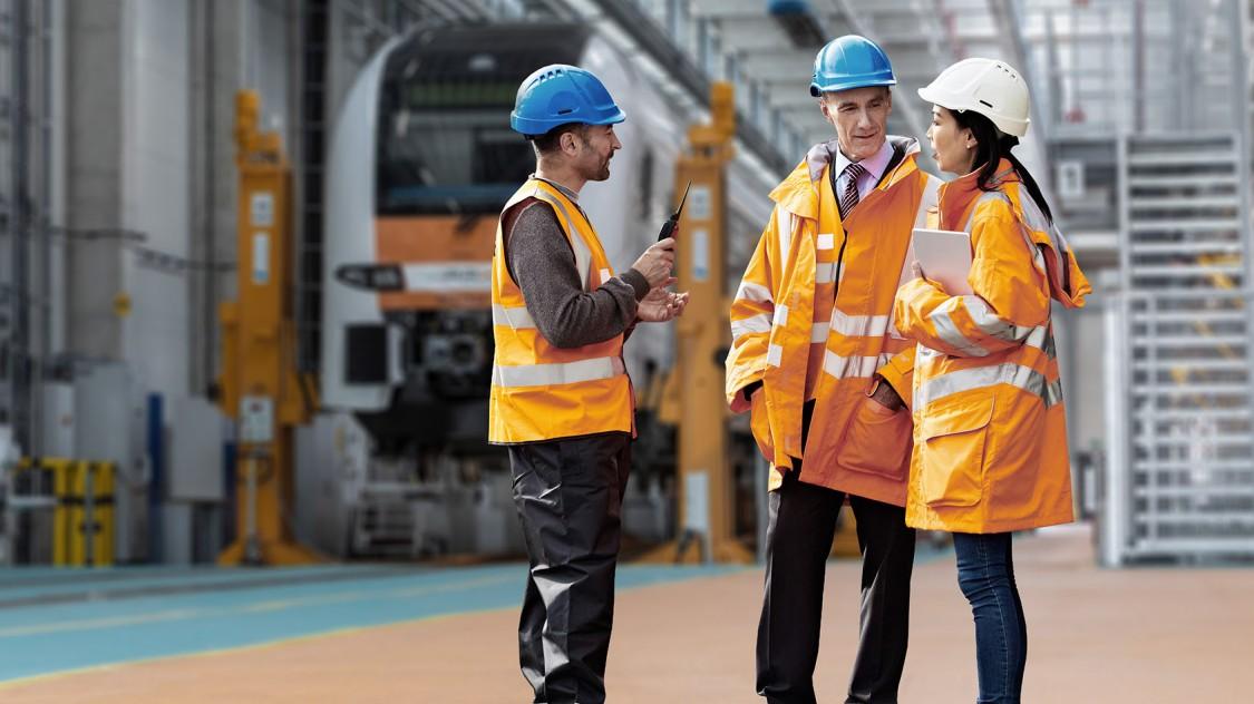 Drei Vertreter der Allianz für Verfügbarkeit, die Sicherheitswesten und Helme tragen, tauschen vor einem Zug im Bahndepo Informationen aus