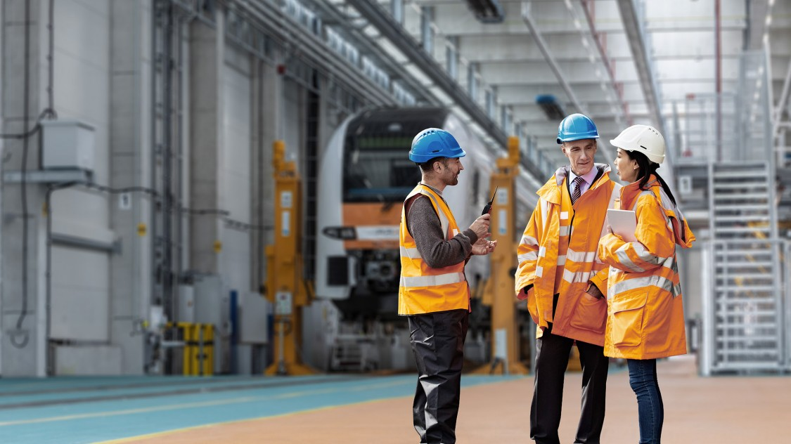 Three representatives of the Alliance for Availability wearing safety vests and helmets are gathering together in a rail depot exchanging information in front of a train