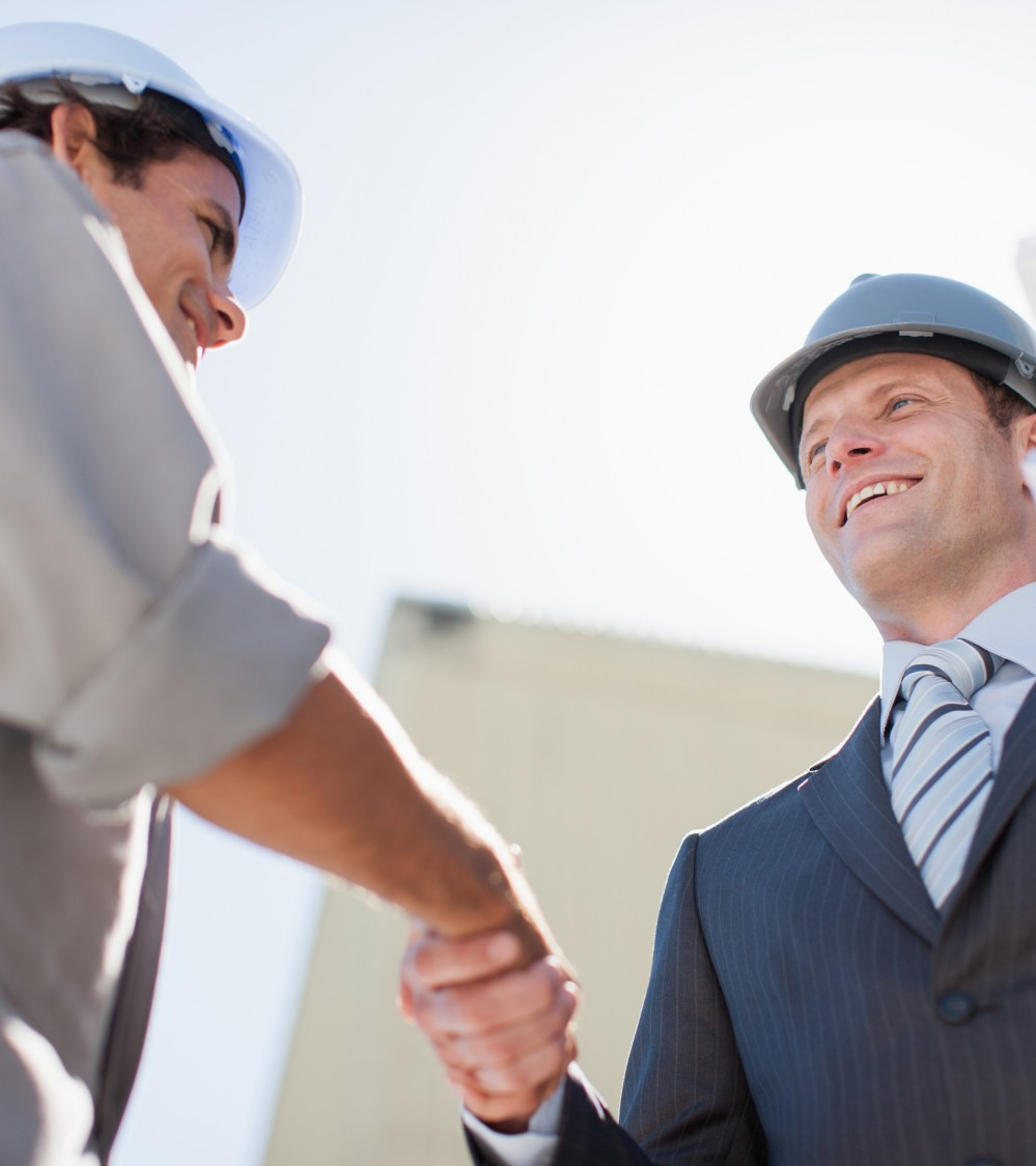Two engineers shaking hands over job specification