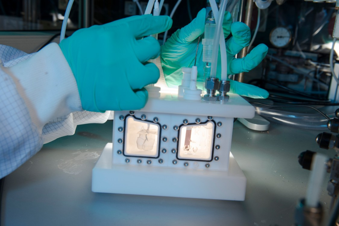 Close-up auf ein paar Hände in Gummihandschuhen, die an einem Elektrolysegerät arbeiten.