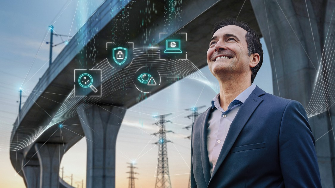 A man stands in front of an elevated highway with electrical power lines in the background. The digital layer has four icons representing what needs to be done (identify, protect, detect, manage) to establish cybersecurity for critical infrastructure networks.
