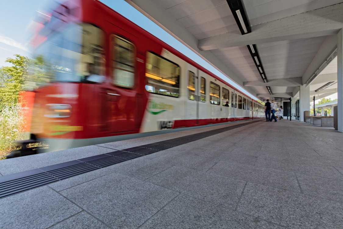 rotweisser Zug verlässt einen leeren Bahnhof