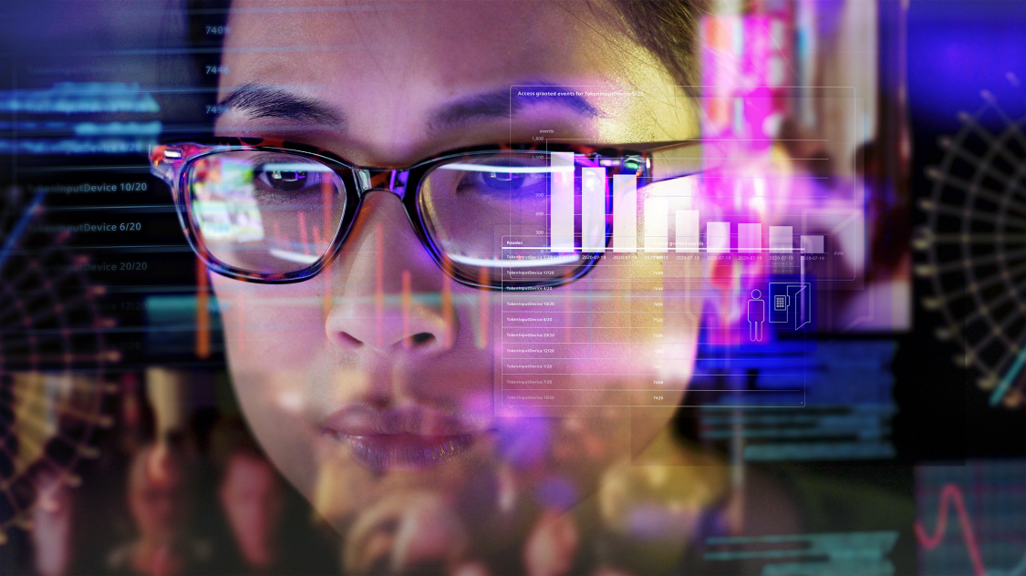Woman looking closely at analytics and data reflection on glass