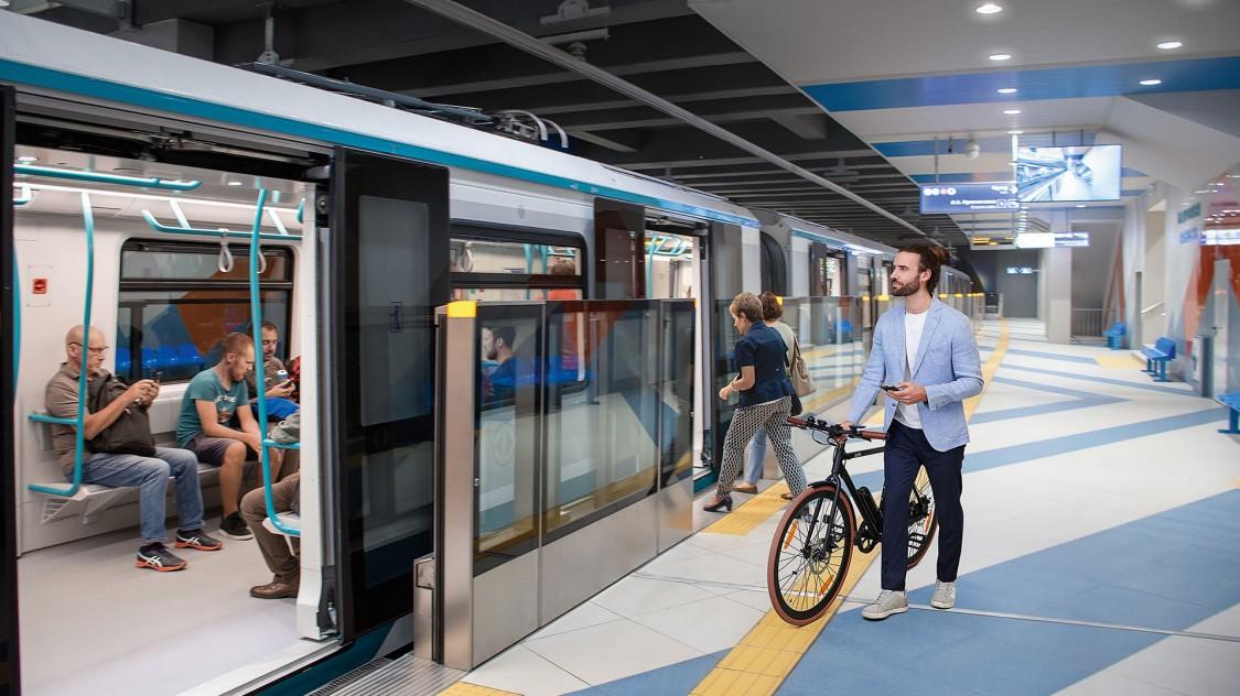 Ein Mann geht mit seinem Fahrrad an einem Bahnsteig in Sofia entlang und macht sich zum Einsteigen in die Siemens Mobility Inspiro Metro bereit.