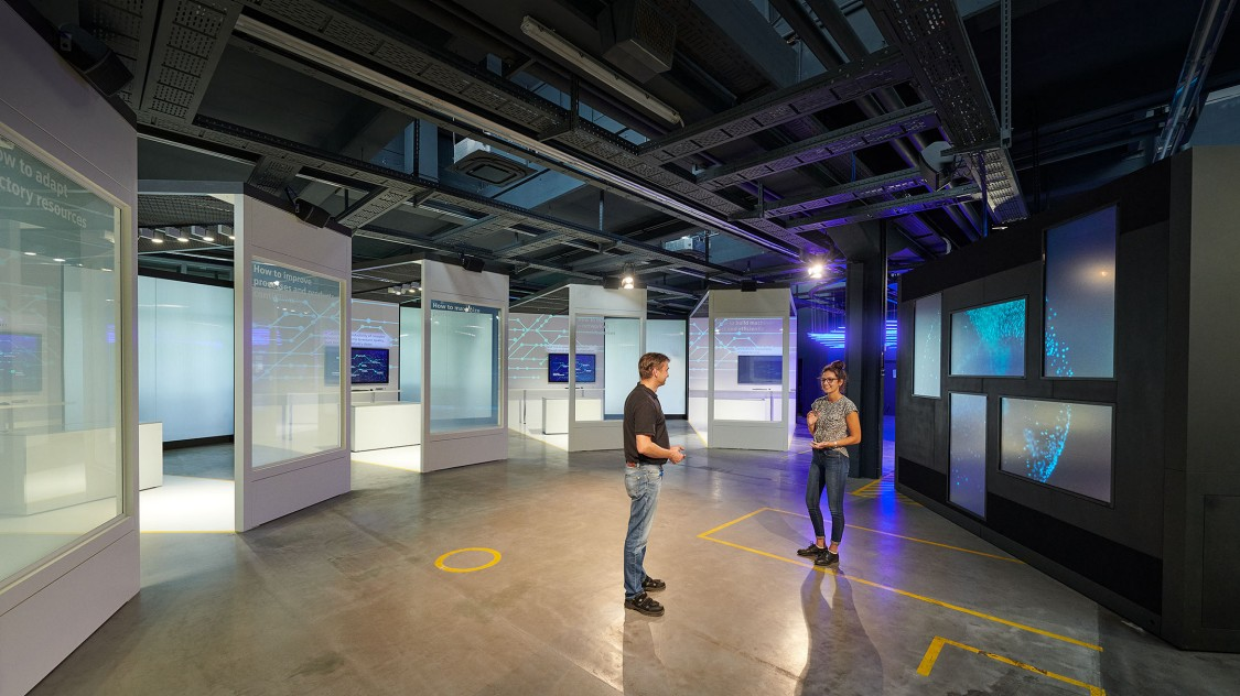 Two people talking about digital transformation in front of the theme rooms of the Arena of Digitalization.