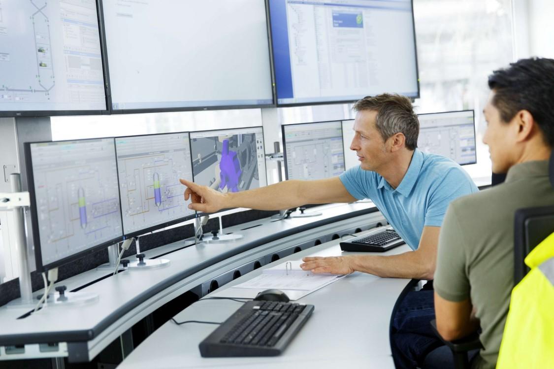 Bild von Personen in einer Telecontrol-Leitstelle vor Monitoren