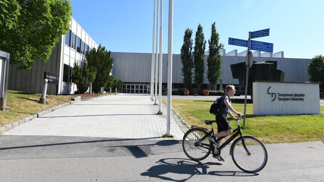 Ein Student verlässt mit seinem Fahrrad den Campus der Tampere University.