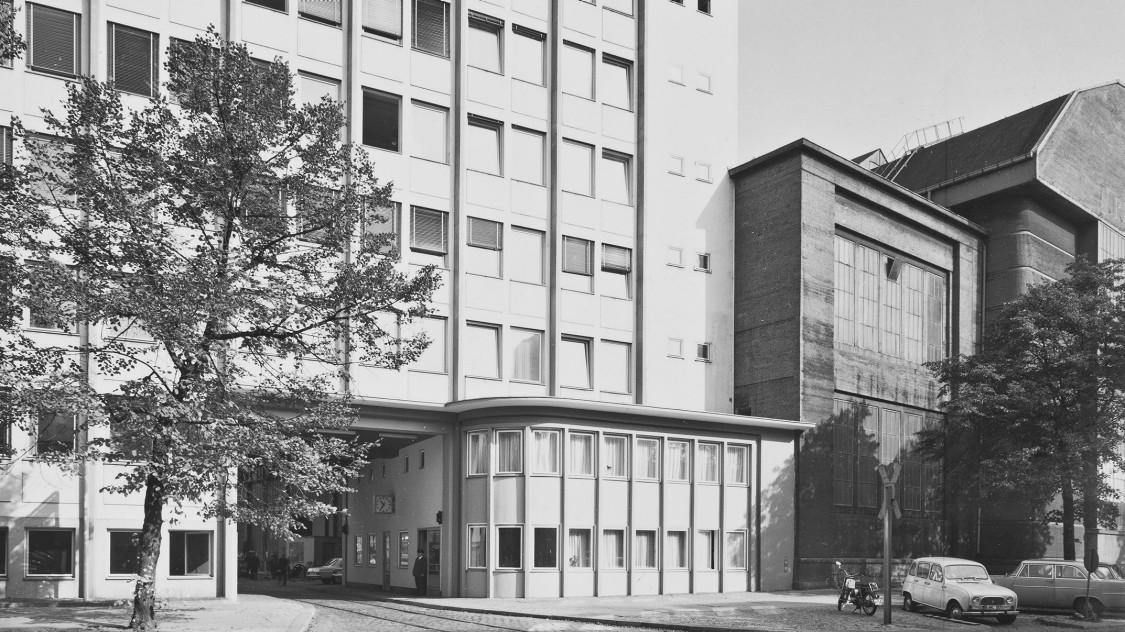 Ab 1956 errichtet die AEG-Turbinenfabrik an der Huttenstraße ein neues Verwaltungsgebäude. Seine Ostseite integriert das Pförtnerhäuschen der Toreinfahrt. Das Verwaltungsgebäude schließt nahtlos an das Seitenschiff der Montagehalle an und verdeckt dieses auf einer Breite von rund 16 Metern