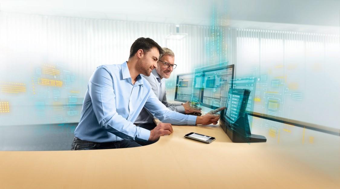 Dva pracovníci studující nástroj pro výběr TIA Selection Tool na jednom ze tří monitorů s efekty digitalizace