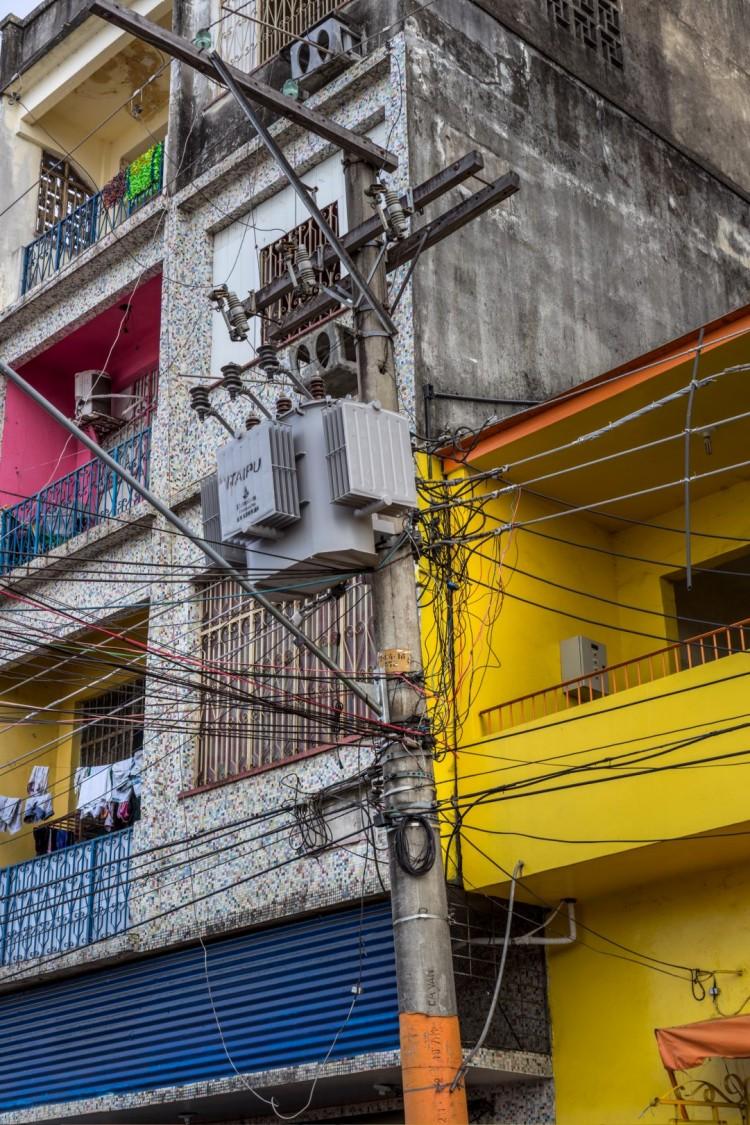 Poste elétrico tomado por cabos de gatos representando o roubo de energia elétrica
