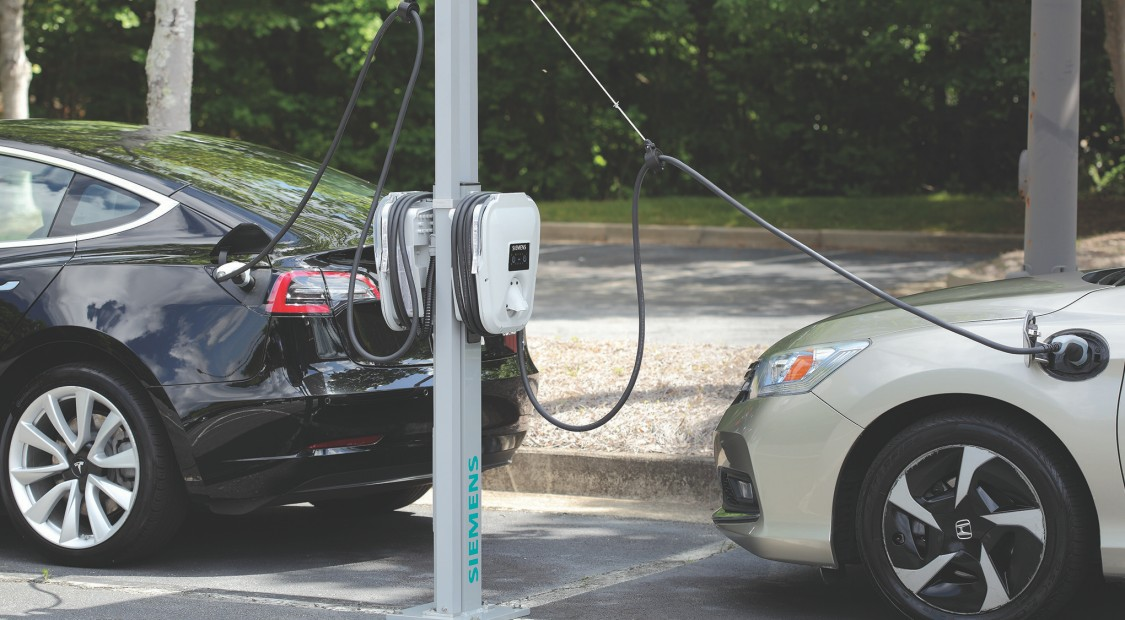 Black and white vehicles at a charging station