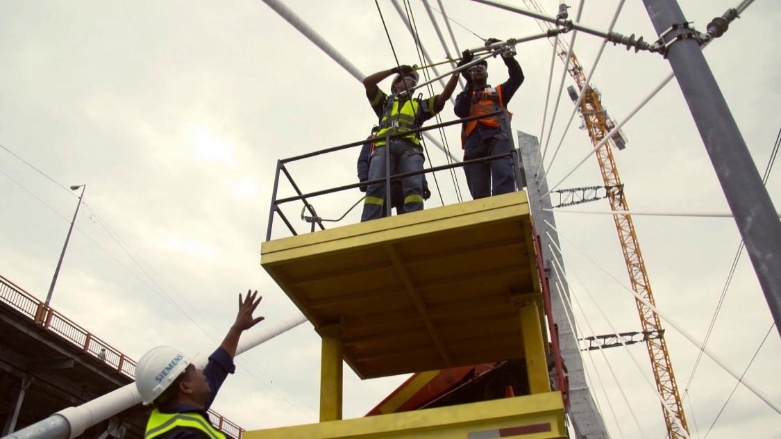 Zwei Arbeiter befestigen eine Oberleitung für ein Bahnsystem