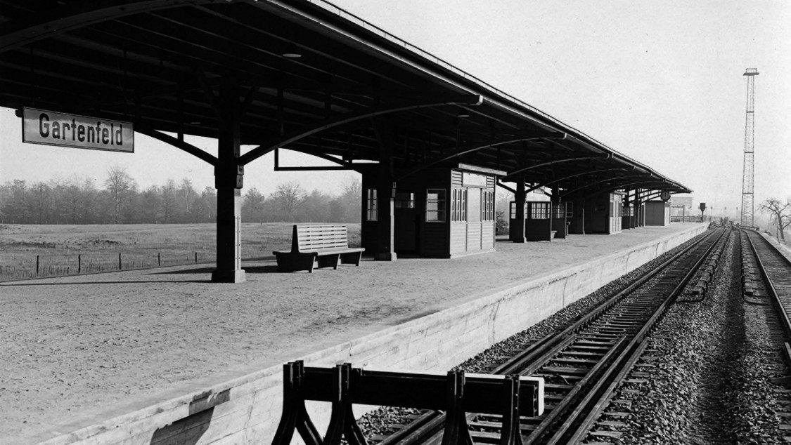 Gartenfeld station: The Gartenfeld station also included an apartment house for company officials. The Kabelwerk and SSW's Metallwerk were about five minutes away by foot. A large holding area was set up between the Siemensstadt and Gartenfeld stations. Two full-size trains – each with eight cars – were parked on each of its six siding tracks after the morning commute, and went back into operation for the evening commute. One special feature of this station was its two 30-meter masts that held the spotlights to light the station – the first system of its kind in Germany.