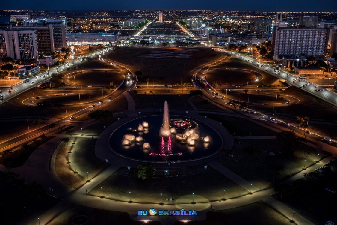 Imagem aérea noturna de cruzamento em grande cidade toda iluminada por energia elétrica
