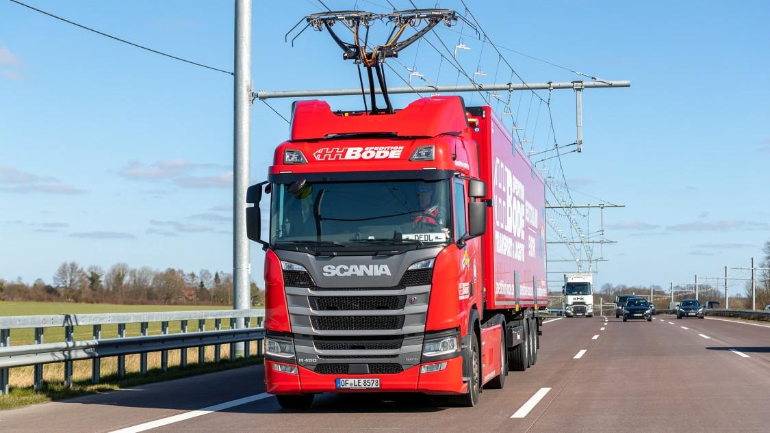 Ein roter LKW mit Stromabnehmern auf dem Dach der Zugmaschine auf einer Autobahn. Über der Fahrbahn verläuft eine Oberleitung.