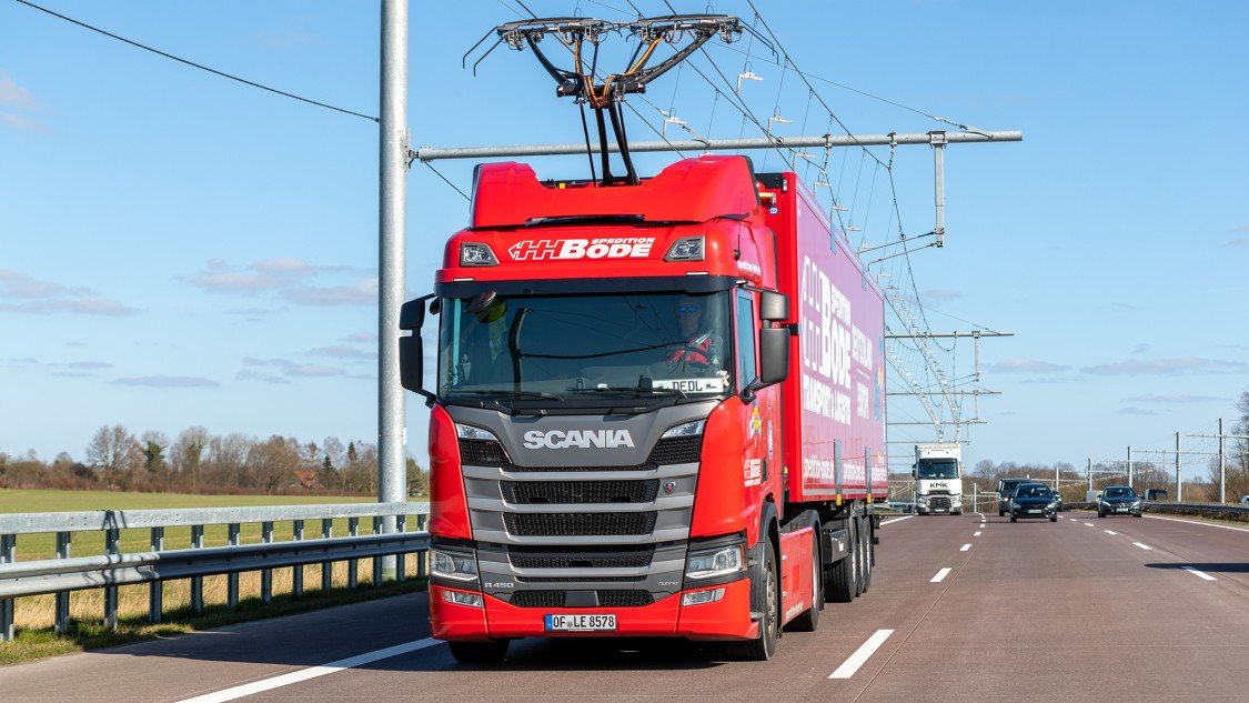 A red truck with current collectors on the roof of the tractor unit on an Autobahn. A catenary system runs overhead.