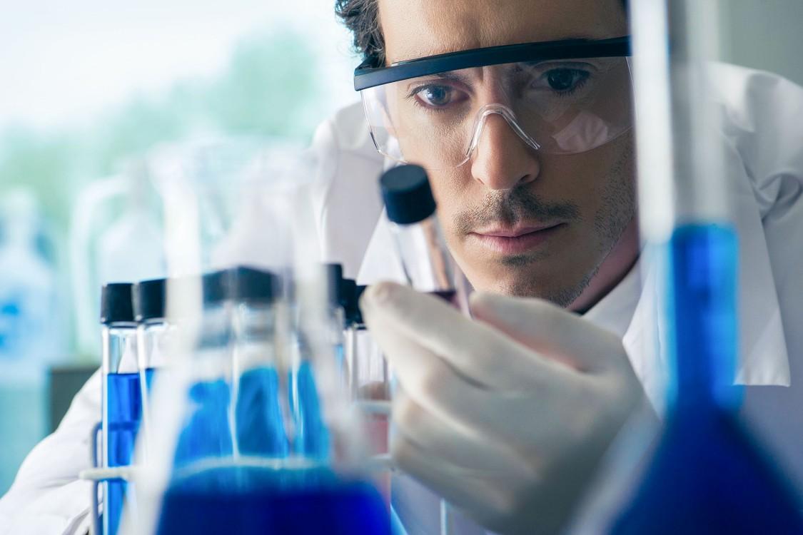 Male scientist assessing medical test tubes