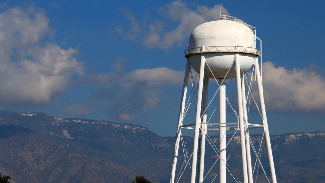 We see a water tower in front of a mountain range and under a blue, with white clouds traversed sky.