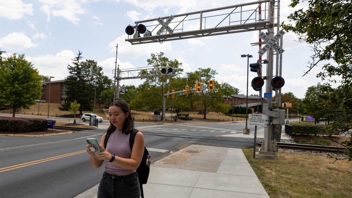 girl walking by rail crossing