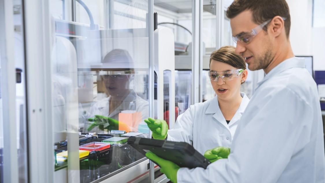 Чоловік і жінка в захисних костюмах працюють з промисловим планшетним комп'ютером у фармацевтичній лабораторії компанії BioNTech.