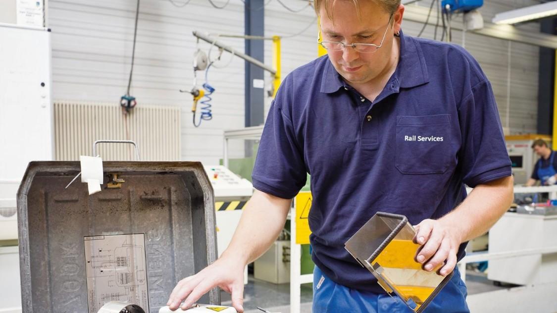 Service Techiker von Siemens wartet einen Weichenantrieb