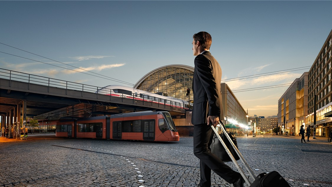 Man carrying a suitcase in front of a Siemens train