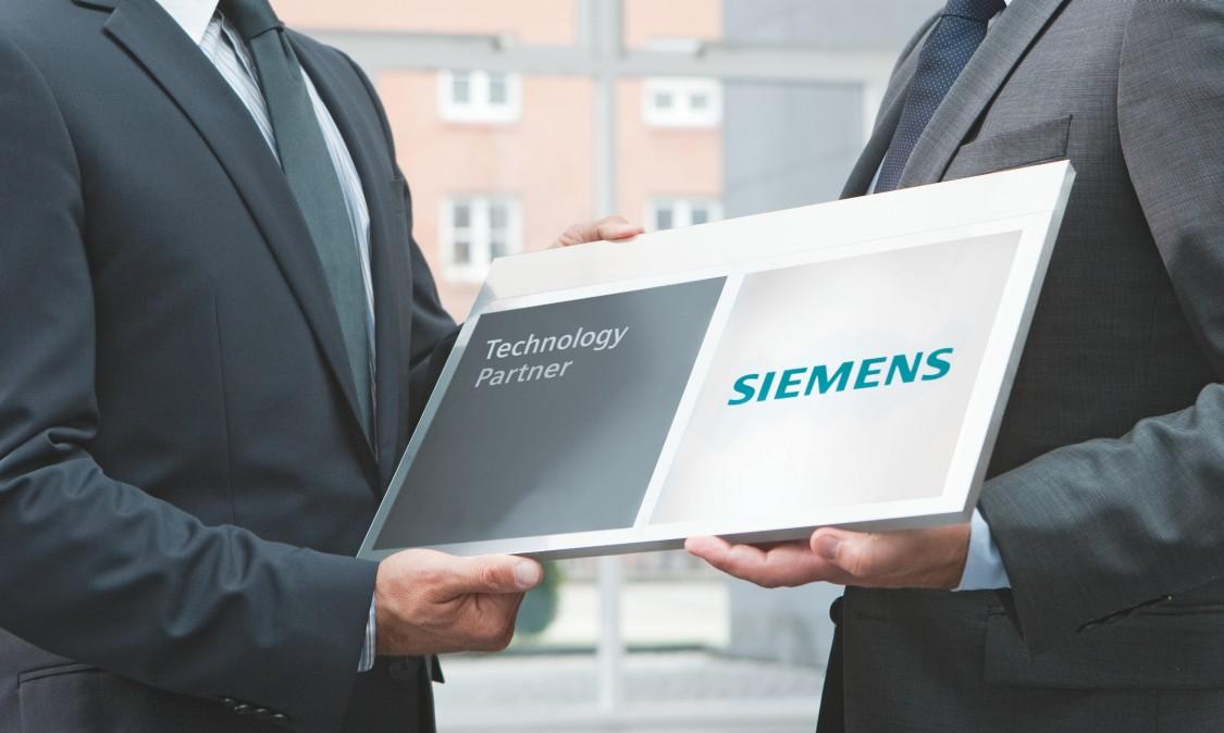 Simoprime. Dois homens de terno seguram ao mesmo tempo uma placa do Technology Partner o programa de parceria de paineis elétricos da siemens
