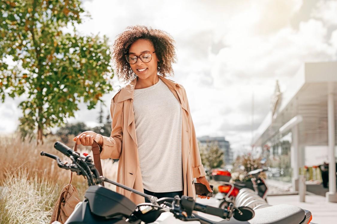 Eine Frau Ende 20 ist im Begriff, auf einen Elektroroller zu steigen. Im Hintergrund stehen noch mehr Elektroroller vor einer urbanen Kulisse.