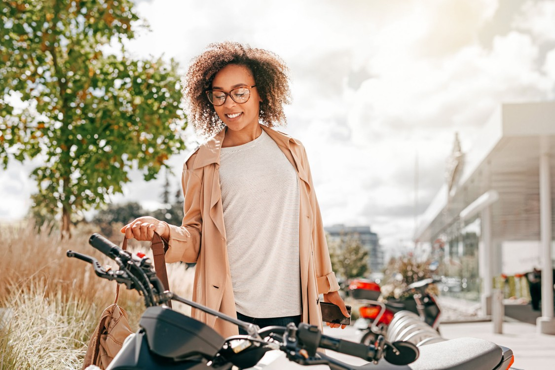 A woman in her late 20s is about to get on an electric scooter. More electric scooters are in the background, with an urban backdrop.