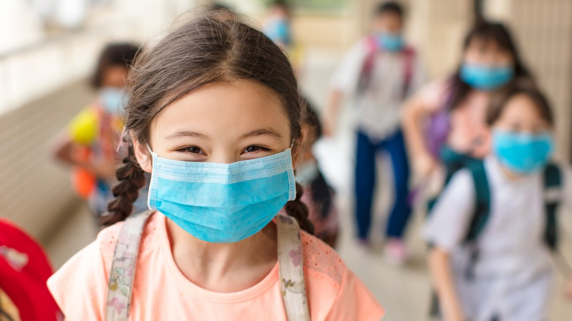 Picture of an elementary school girl in the hallway with her friends, smiling and social distancing wth masks